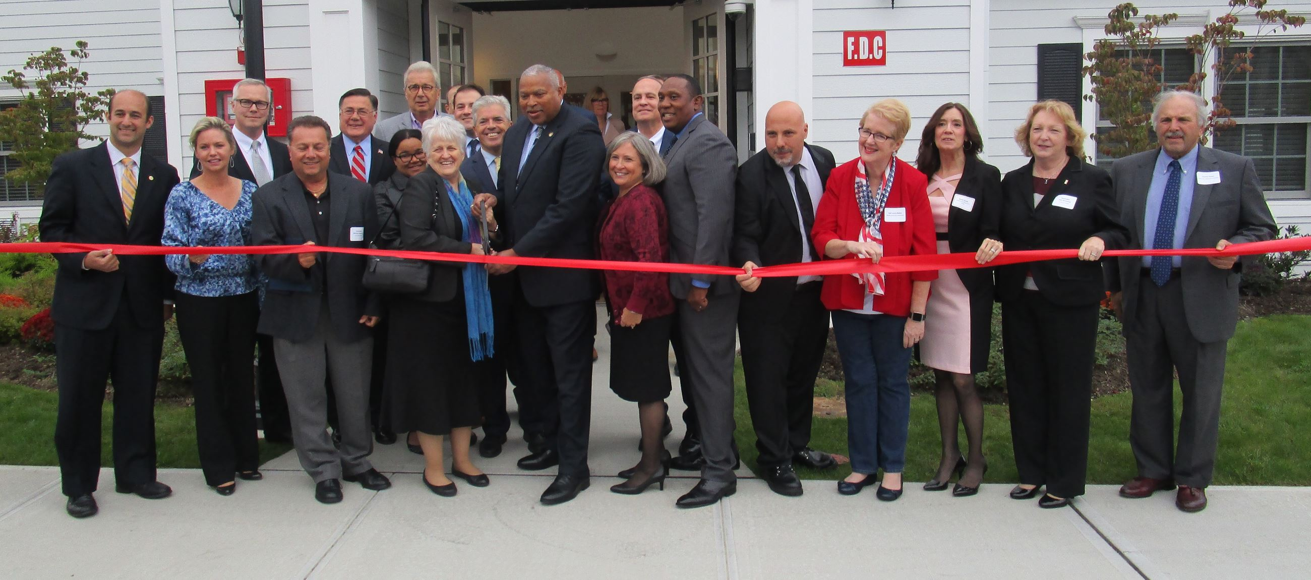 Elected officials and community leaders cut the ribbon at Renaissance Village.