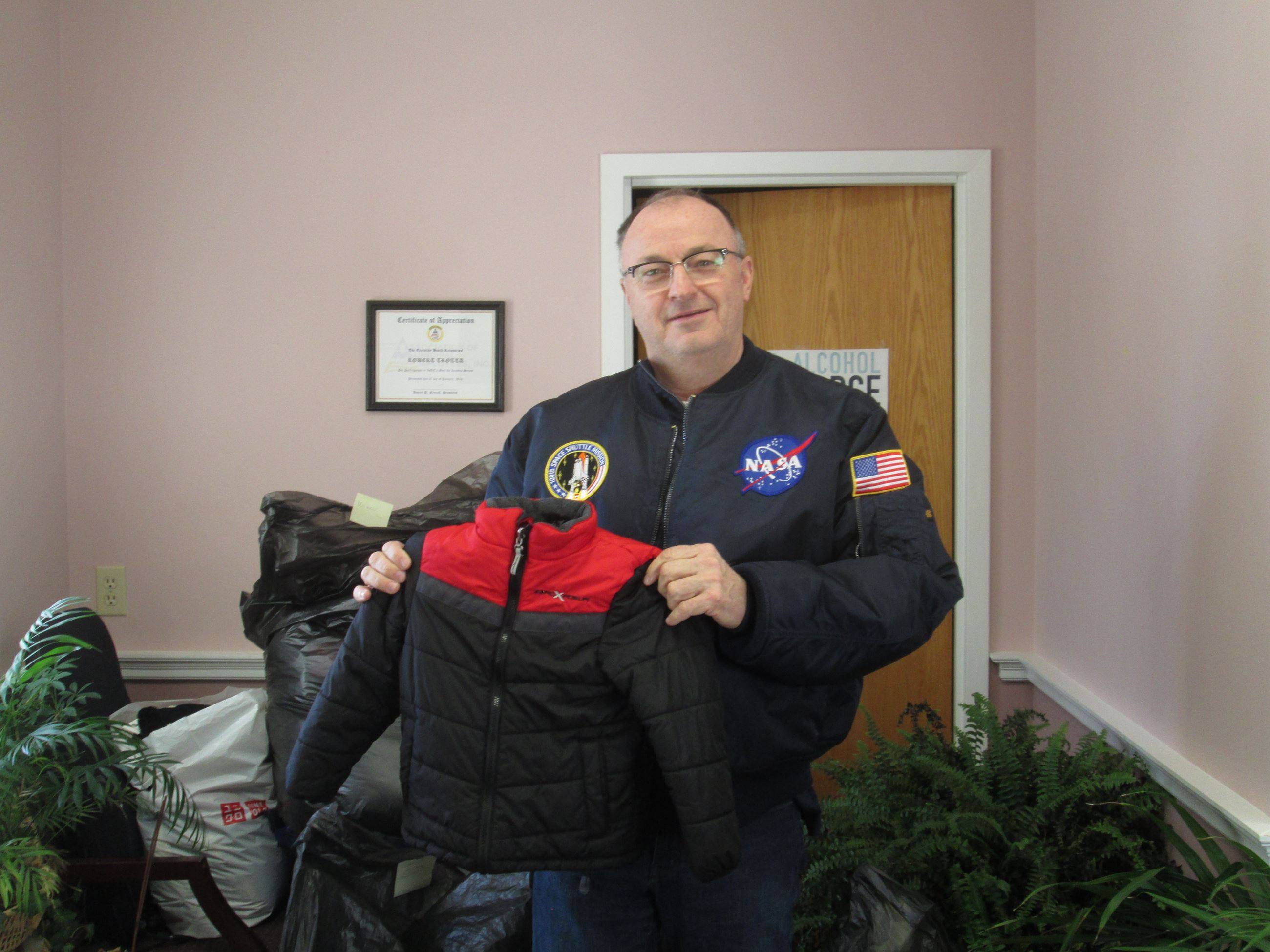 Legislator Trotta is pictured with some of the coat donations, as well as with a brand new jacket fr